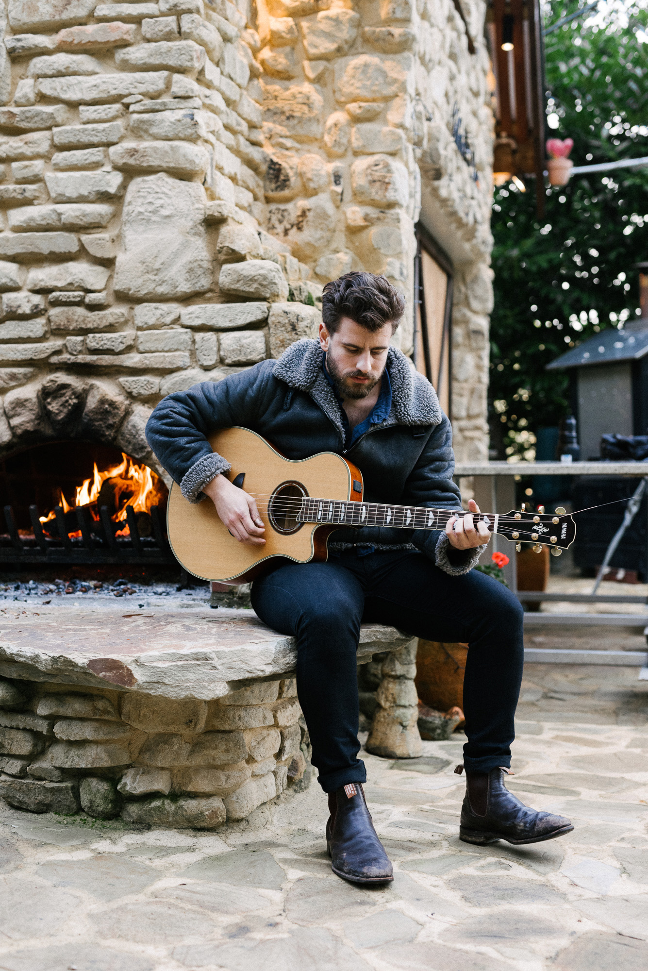 Ollie English playing guitar by open fire